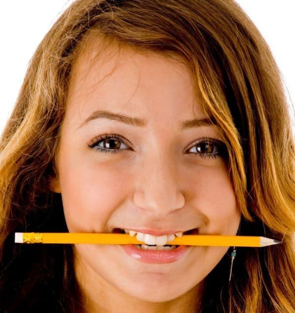 Задържане на молив между зъбите
