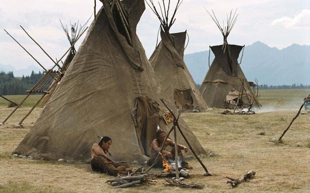 Индианци на стан, почиващи около традиционната палатка типи