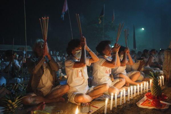 участници във фестивала палят пръчки за своите богове