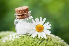 Бели гранули в стъклено шише и цвете