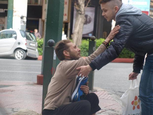 мъж помага на бездомник