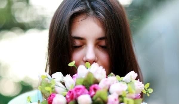 Жена, миришеща букет цветя