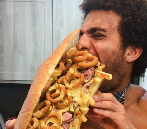 мъж, който яде хамбургер