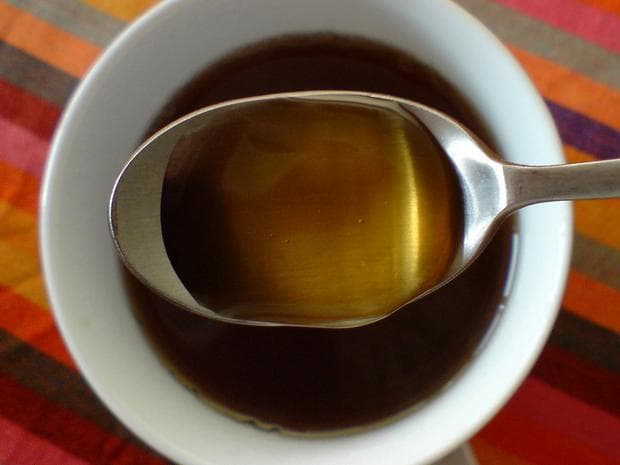 Лтъжица мед над чаша чай