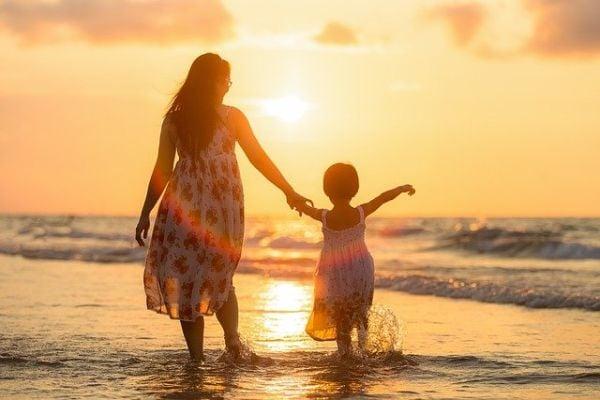 Жена и дете де разхождат по брега на морето