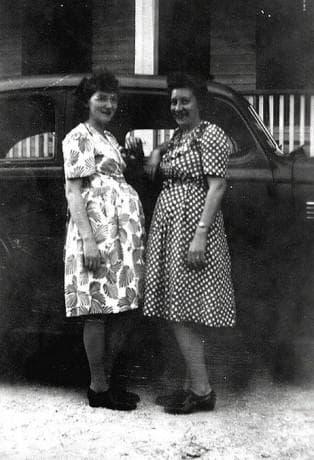 бременни жени, позиращи до кола