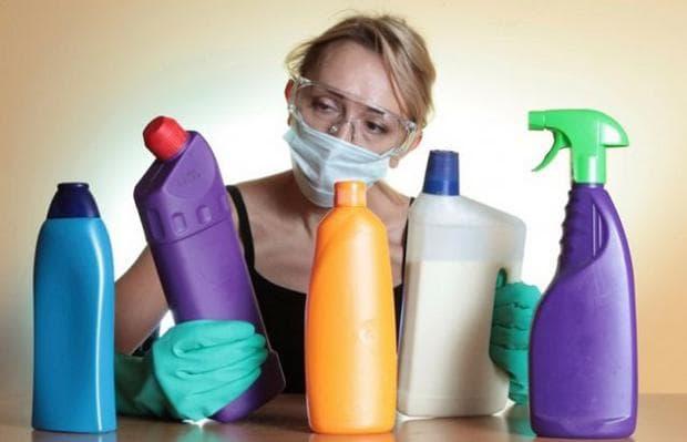 жена държи почистващи препарати