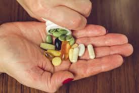 Таблетки и капсули в ръка