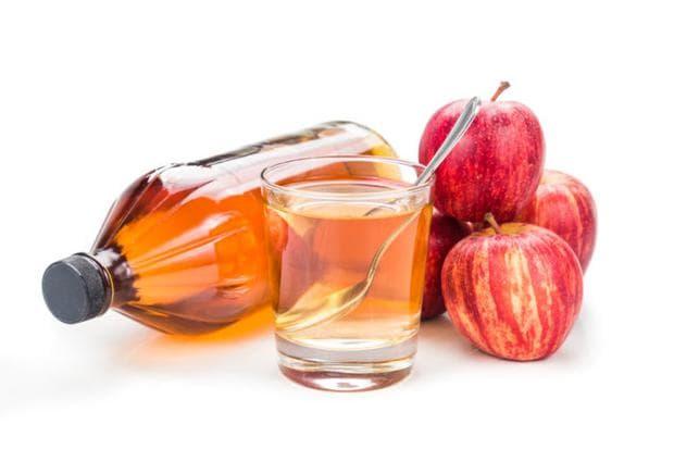 Червена ябълка и ябълков оцет в чаша