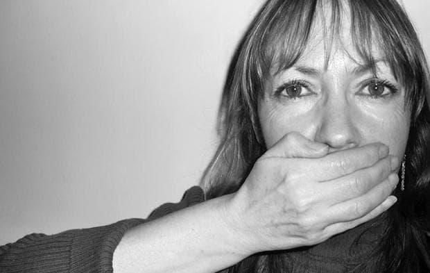 жена прикрива устата си с ръка
