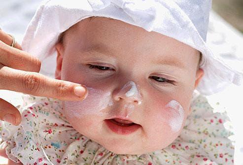 Бебе намазано със слънцезащитен крем