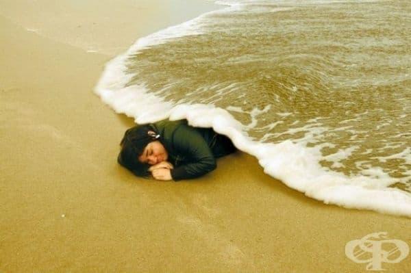 Жена лежи под одеяло от океан.
