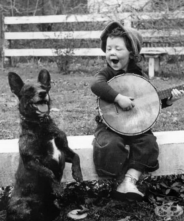Момченце свири и пее с кучето си.