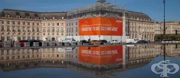 Надписът на тази реклама може да се чете само в отражението на реката. Бордо, Франция.