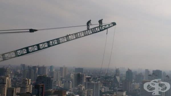 Снимка, направена от 33-ия етаж. Мъжете работят без никакви предпазни средства.
