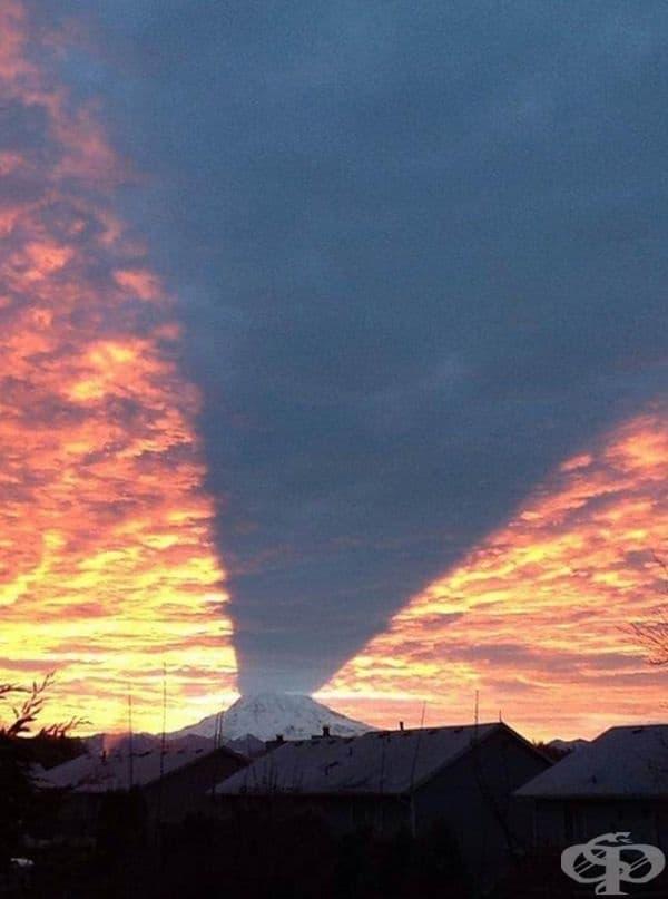 Дъждовен облак, който хвърля сянка по време на залез.