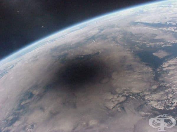 Лунна сянка над Земята по време на слънчево затъмнение.