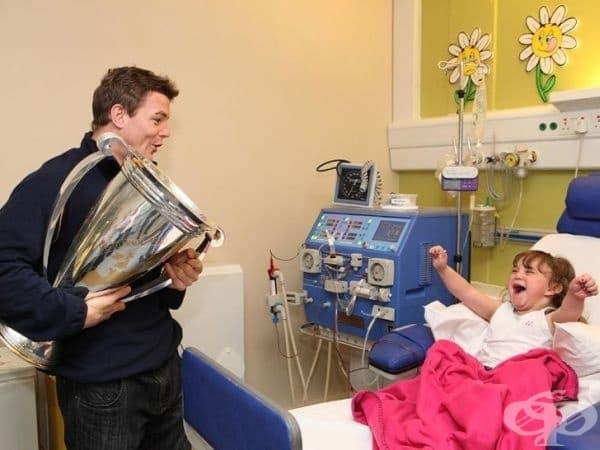 """Брайън О'Дрискол, капитанът на ирландския отбор по ръгби, посещава момиче в болницата с купа на """"Хайнекен""""."""