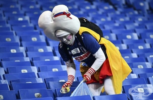 Фенове от Япония събират боклука по трибуните след мача.