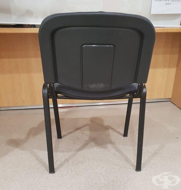Човек, който държи стол.