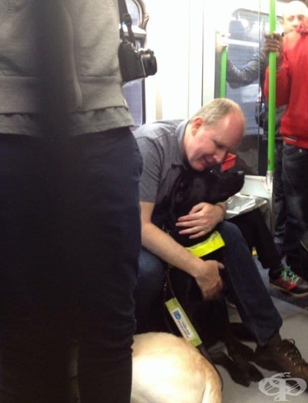 Сляп мъж прегръща своето куче водач.