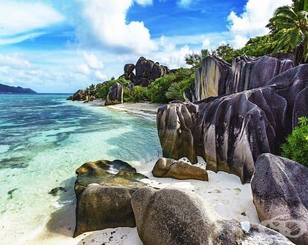 Сейшелските острови. Живописен плаж с бял пясък, поддържан от естествено изваяни гранитни камъни и изумрудени води. Това е един от малкото плажове, обърнати на запад, от който могат да се наблюдават прекрасни залези.