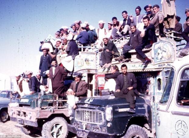 Щастливи граждани се събират върху големите камиони, които служат като преносими трибуни.
