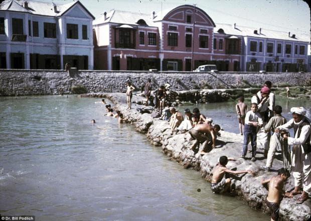 Млади момчета и мъже се къпят, плуват и играят във водите на реката в Кабул