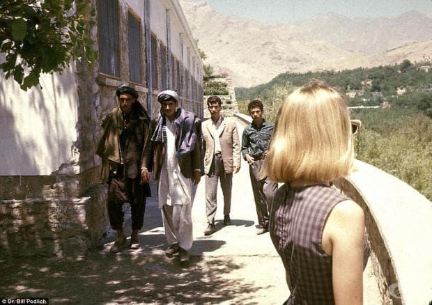 Младата Пег Полдих, снимана точно при пристигането си, докато местни младежи подминават