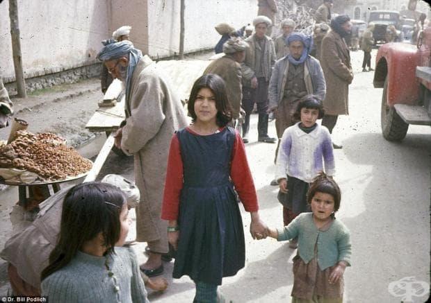 Две сестри позират на фотографа, заобиколени от местните търговци