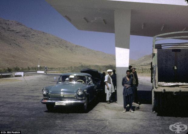 Мъже стоят до паркираните си автомобили на петролна станция