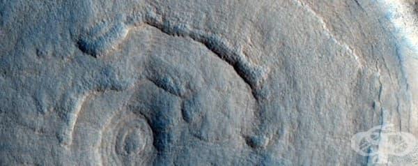 Кратер пиедестал, формиран от ерозиращите по различен начин различни видове скали.