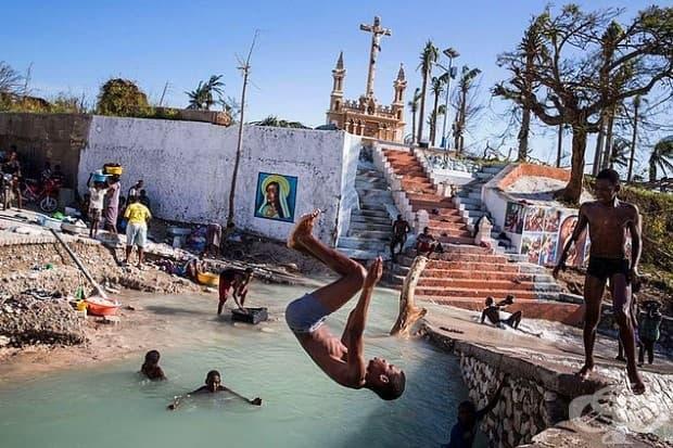 Деца плуват в реката, в която се срути мост в Порт Салут, Хаити. Градът е претърпял сериозни щети от урагана Матей, а много домове са напълно унищожени.