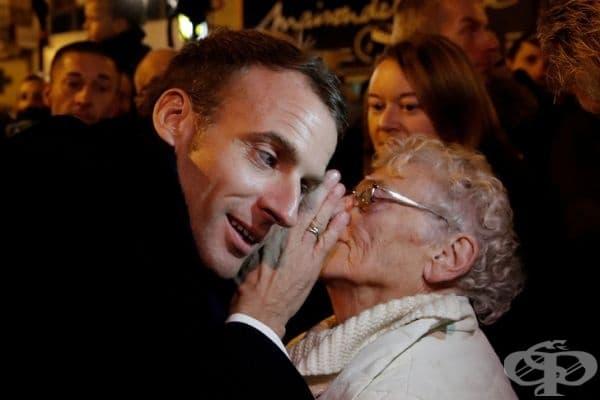 Френският президент Емануел Макрон се опитва да чуе възрастна жена в тълпата.