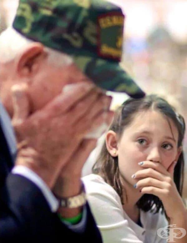 Внучка наблюдава своя дядо по време на церемония по случай деня на ветераните.