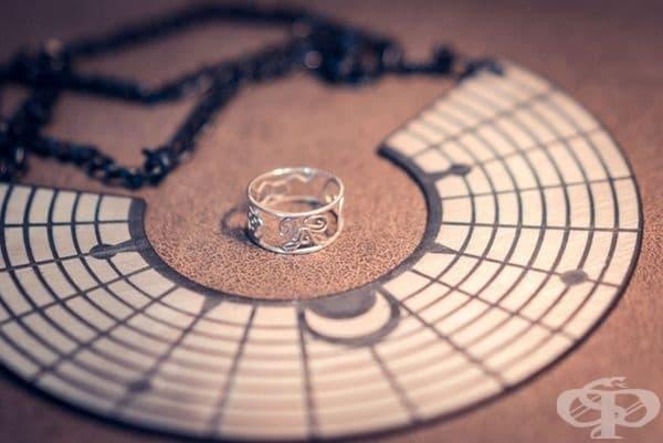 """Дизайнът на сватбените пръстени. Той е разработен по идея на Жил Бонули. Съчетава инициалите на младоженците, спиралата на Фибоначи, изображение на молекулата на серотонина като символ на вечното щастие и сакралната геометрична фигура """"Цветето на живота""""."""
