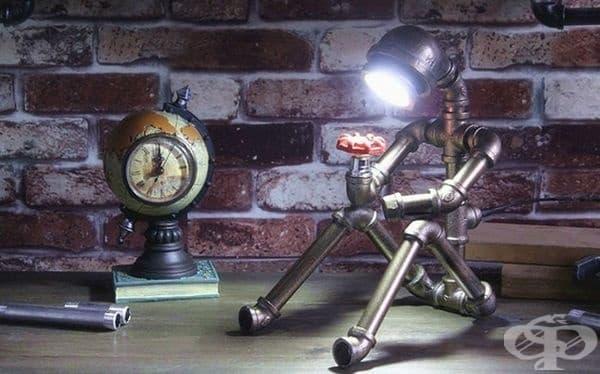 Настолна лампа във формата на човек, изработен от водопроводни тръби.