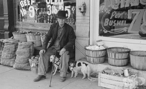 Мъж и кучета пред хранителен магазин в Илинойс, 1940 г.