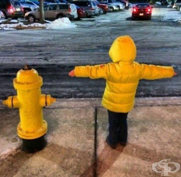 Пожарен хидрант и дете в жълто яке.