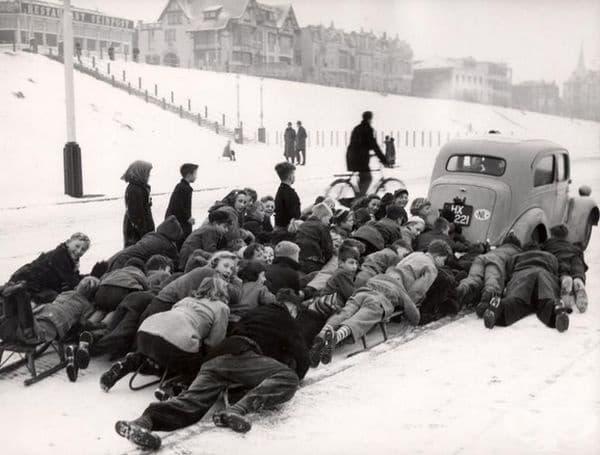 Деца върху шейни, изтегляни по снежен път в Шевенинген, Холандия. Датата е неизвестна.