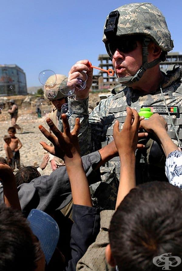 Капитанът на американската армия Майкъл Уикстром забавлява афганистански деца със сапунени мехурчета.