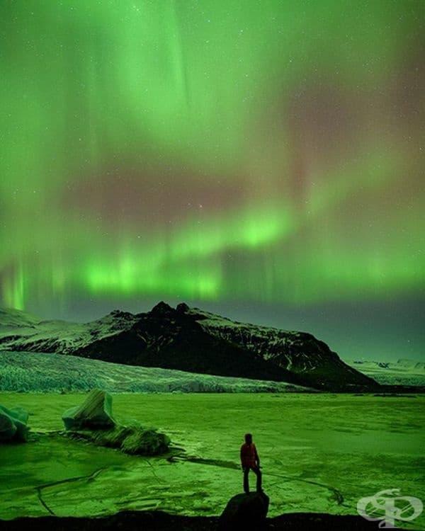 Снимка на масивен ледник, осветен от Северното сияние в югоизточна Исландия.