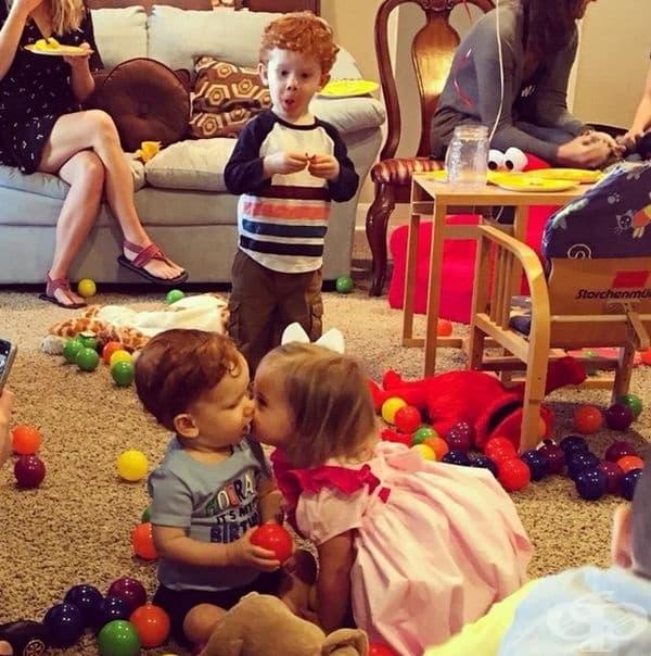 """""""Големият брат наблюдава малкия си брат как получава първата си целувка от дама на рождения си ден."""""""