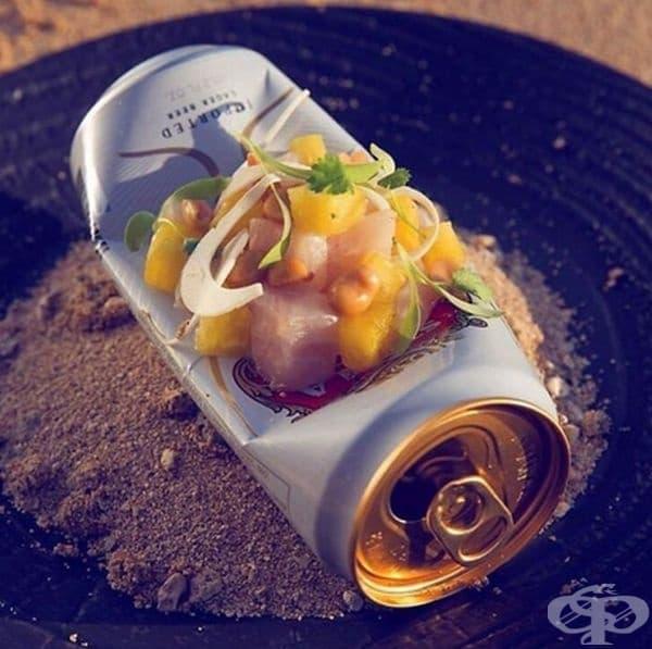 Риба, сервирана върху празна кутия от бира на непочистен пепелник.