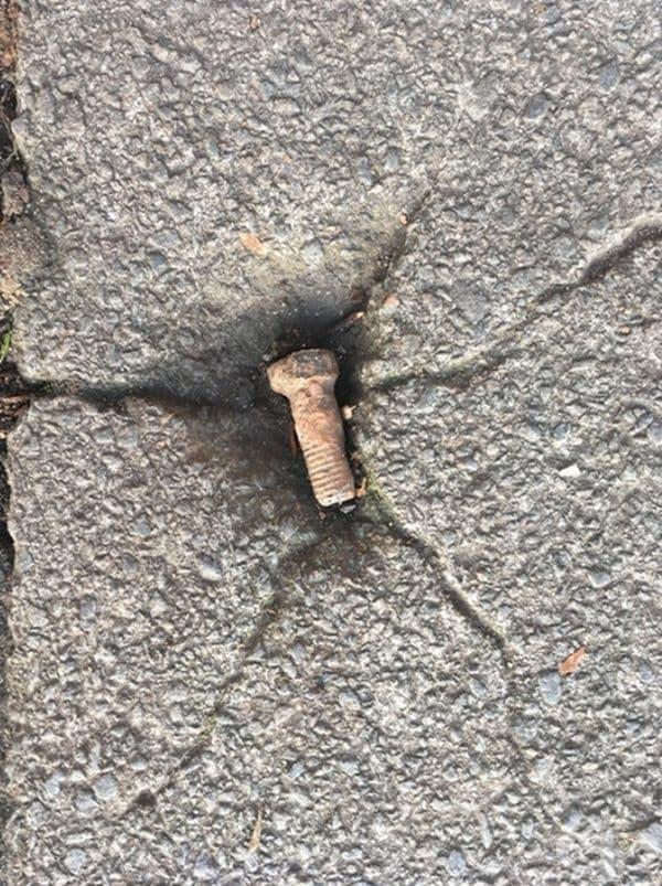 Този винт в пукнатина на тротоара сякаш е паднал от сериозна височина.