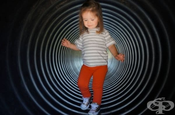 Малко дете в тунел за игра.