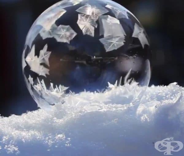 Еднакво разположени снежинки по повърхността на сапунено балонче.