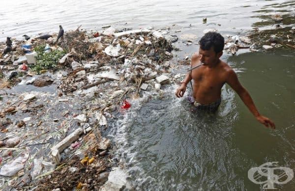 Момче от Индия си мие зъбите в река Ганга.