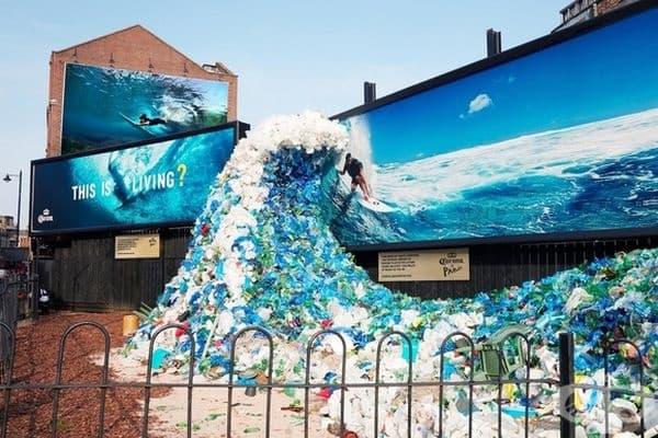 """Табелата под билборда посочва: """"Тази вълна от отпадъци съдържа средното количество на пластмасови отпадъци в морето, открито на всеки 2 мили от плажа във Великобритания""""."""
