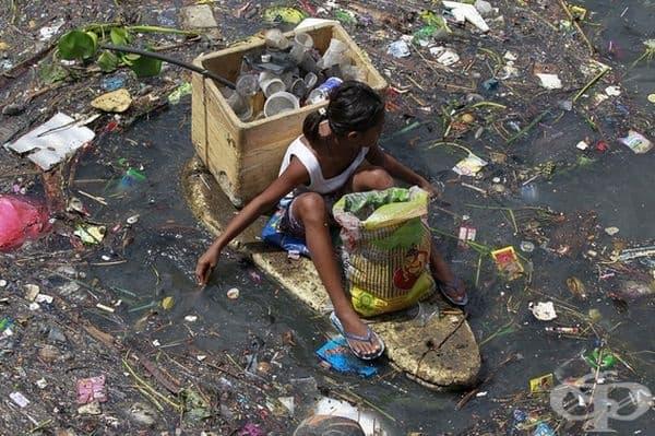 Момиче плава с импровизиран сал по средата на замърсена река в град Навотас, на север от Манила.